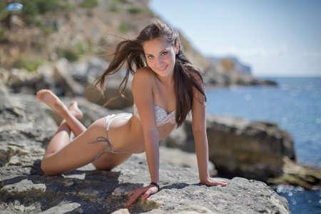 rocks water: Girl on rocky seashore. Young woman in bikini posing on the beach looking at camera smiling
