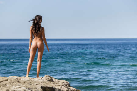 Girl at the sea. Naked young woman stands on rocky seashore, rear view