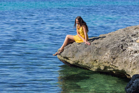 eastern european ethnicity: Girl at the sea. Young woman in yellow dress sits on rock