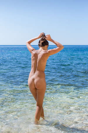 nude nature: Girl at the sea. Naked young woman enters the sea water, rear view