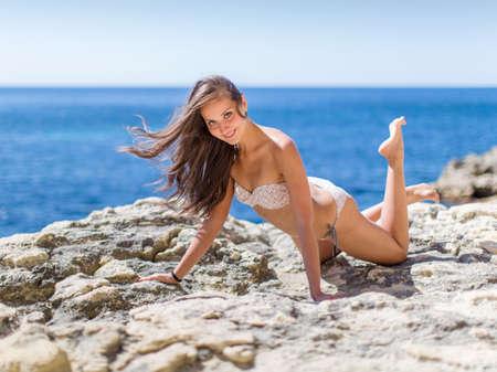 seashores: Girl on rocky seashore. Young woman in bikini posing on the beach looking at camera smiling