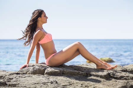 russian ethnicity: Girl at the sea. Young woman in pink bikini sits on rock, side view Stock Photo