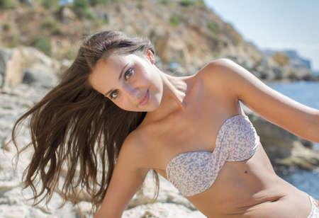 girl pose: Girl on rocky seashore. Young woman in bikini posing on the beach looking at camera smiling