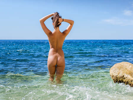 Girl at the sea. Naked young woman enters the sea water, rear view