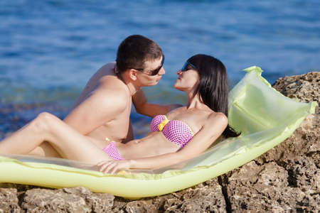 open girl: Attractive couple at the sea. Young man and woman on wild rocky seashore Stock Photo
