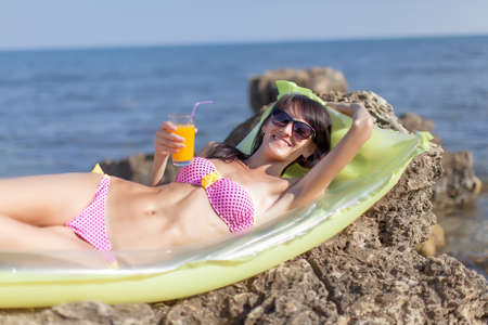seashores: Girl on rocky seashore. Slim young woman in bikini lying down on pool raft with glass of juice in hand. She looks through tinted sunglasses at camera smiling Stock Photo