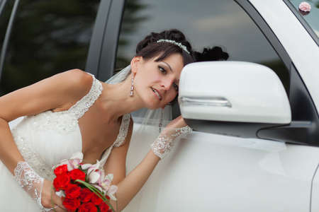 russian ethnicity caucasian: Bride near the car. Attractive bride looks in rearview mirror of wedding car