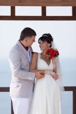 eastern european ethnicity: Newly wedded on open air. Just married in day of them wedding posing against the sea