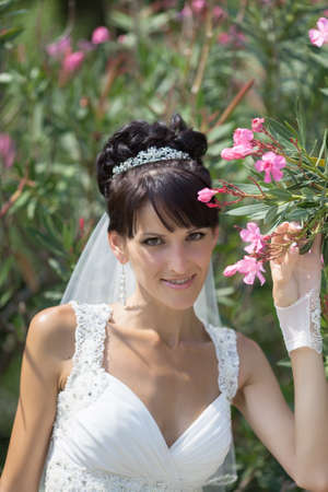 russian ethnicity: Bride in the park. Portrait of attractive young bride posing with flowers of oleander