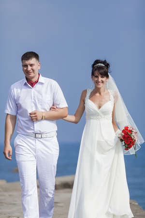 newly wedded couple: Newly wedded couple on seafront. Just married in day of them wedding walking along seashore