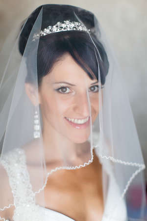 eastern european ethnicity: Portrait of bride indoors. Attractive young bride looking at camera through wedding veil