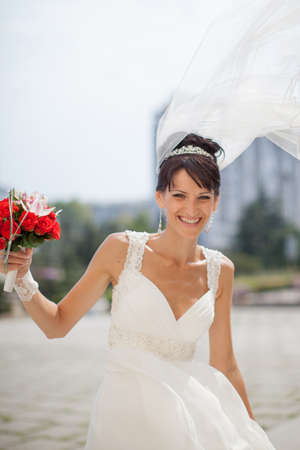 russian ethnicity: Bride in the park. Portrait of attractive young bride with nosegay