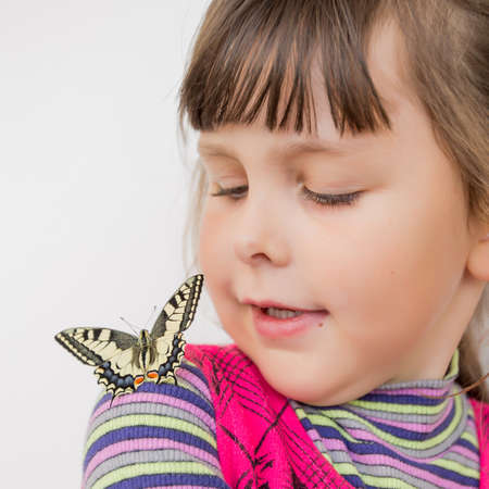 russian ethnicity: Child and butterfly. Portrait of preschooler girl with papilio machaon