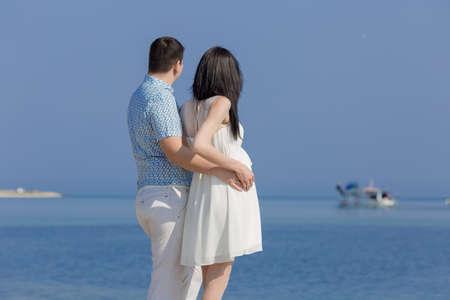 mujer mirando el horizonte: joven pareja en el mar. joven abrazando a su mujer embarazada. Pareja observando el yate que mira en distancia