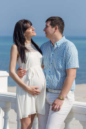 russian ethnicity: Attractive couple on seashore. Young man embracing his pregnant wife on seafront, looking each on other Stock Photo