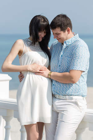 russian ethnicity caucasian: Attractive couple on seashore. Young man touching abdomen of his pregnant wife