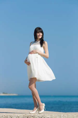 expectant: Expectant mother on the seafront. Pregnant woman in white dress posing at the sea