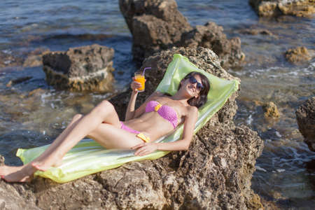 open  women: Girl on rocky seashore. Slim young woman in bikini lying down on pool raft with glass of juice in hand. She looks through tinted sunglasses at camera smiling Stock Photo