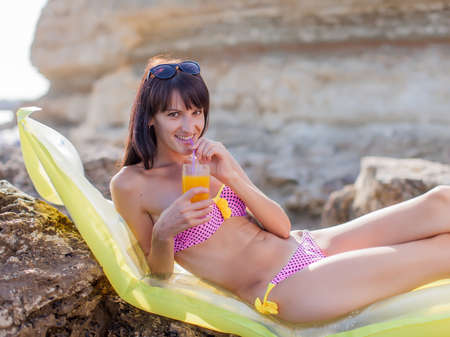 seashores: Girl on rocky seashore. Slim young woman in bikini lying down on pool raft with glass of juice in hand. She looks at camera smiling