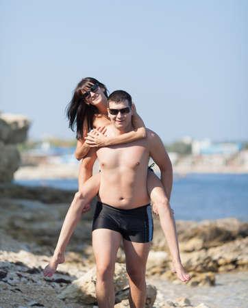 seashores: Piggyback. Young man carries girl on his back along wild rocky seashore