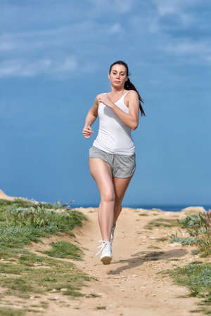 eastern european ethnicity: Jogging. Woman in white tank top and gray sports briefs runs along seashore