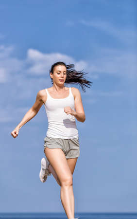 briefs: Jogging. Woman in white tank top and gray sports briefs runs along seashore
