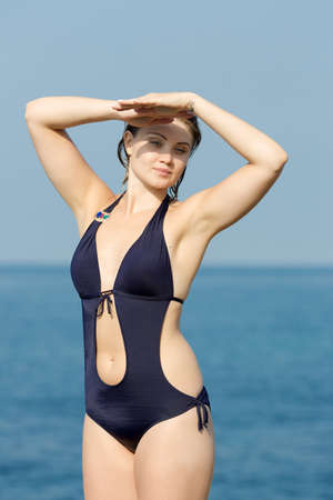 russian ethnicity: Portrait of girl after swimming. Wet young woman in one-piece swimsuit covering her eyes from the sun