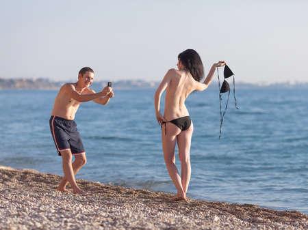 Attraktive Paare in dem Meer. Junger Mann nimmt Foto mit Telefon seiner topless Freundin Standard-Bild