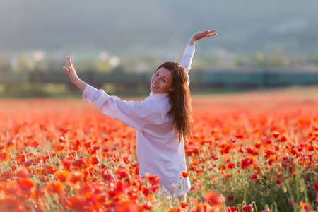 non urban 1: Girl at blooming poppy field. Young woman looking over shoulder standing in poppy field Stock Photo