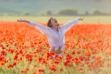 half dressed: Girl at blooming poppy field. Young woman posing in poppy field in evening time