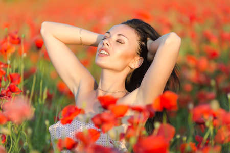 flower head: Girl at blooming poppy field. Young woman posing in poppy field in evening time