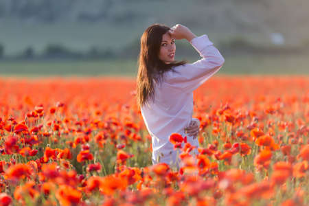 non urban 1: Girl at blooming poppy field. Young woman posing in poppy field in evening time