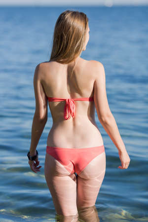enters: Girl at the sea. Young woman enters the sea water, rear view