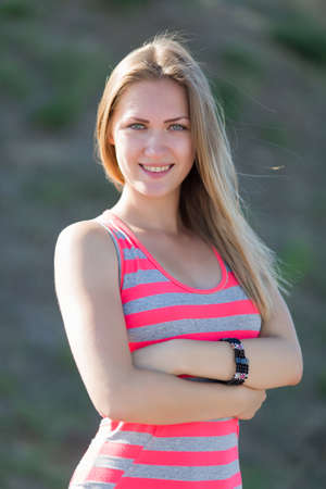 waist up: Female waist up portrait. Long haired blonde standing with folded arms in striped dress Stock Photo