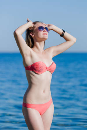 pink bikini: Girl at the sea. Young woman in pink bikini and sunglasses corrects her hairstyle