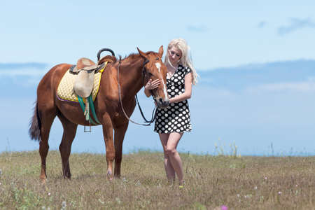 gelding: Gelding and blonde woman. Young blonde woman in polka-dot dress with brown horse.