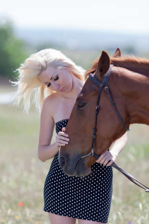 gelding: Blonde woman stroking gelding. Young blonde woman in polka-dot dress with brown horse