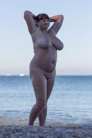 Overweight middle aged woman at the sea. Alone naked woman posing with arms raised in shadow on seashore Stock Photo