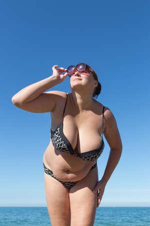 Übergewichtige Frau mittleren Alters am Meer. Übergewichtige Frau mittleren Alters blickt auf Sonne durch getönte Sonnenbrille