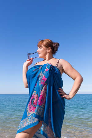 large build: Overweight middle aged woman at the sea. Overweight middle-aged woman wrapped in pareo posing against the sea
