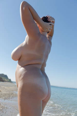 Overweight middle aged woman at the sea. Nude overweight middle-aged woman posing with arms raised