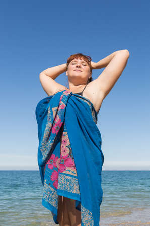 Overweight middle aged woman at the sea. Overweight middle-aged woman wrapped in pareo posing against the sea