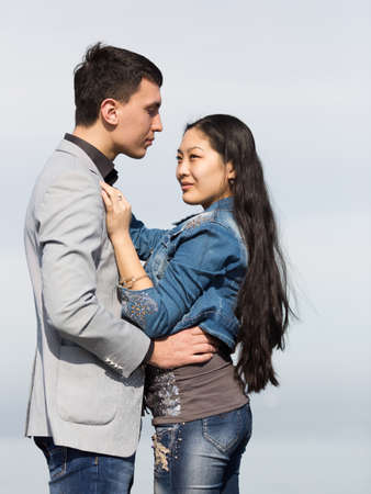 eastern european ethnicity: Attractive couple against of sky. Asian girl and european guy on background of sky