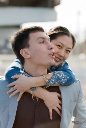 eastern european ethnicity: Piggyback. European guy carrying on shoulders his asian girl Stock Photo