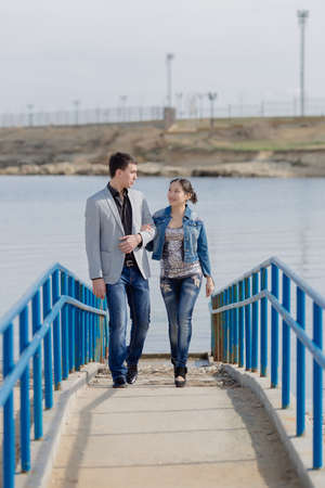 eastern european ethnicity: Attractive couple on seafront. Asian girl and european guy walking along pier Stock Photo