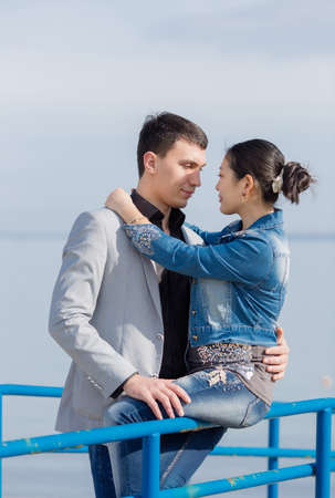 eastern european ethnicity: Portrait of attractive couple on open air. Asian girl and european guy on seashore