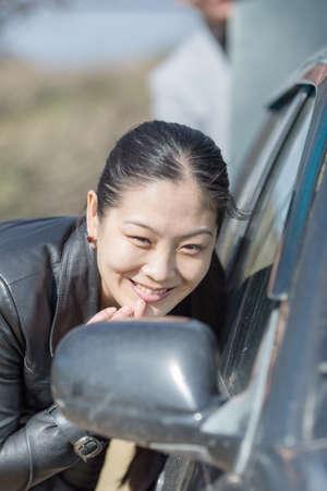 korean girl: Portrait of attractive Korean girl outdoors. Asian girl looking into car mirror