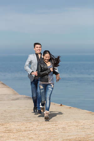 Attractive couple playing catch-up on concrete pier. European guy catches his asian girlfriend