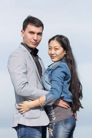 eastern european ethnicity: Attractive couple against of sky. Asian girl and european guy posing on background of sky