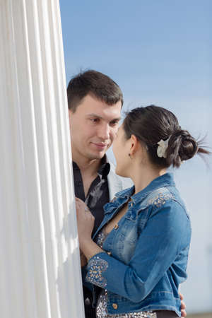 nape: Attractive couple on open air. Asian girl and european guy standing face to face near of column outdoors
